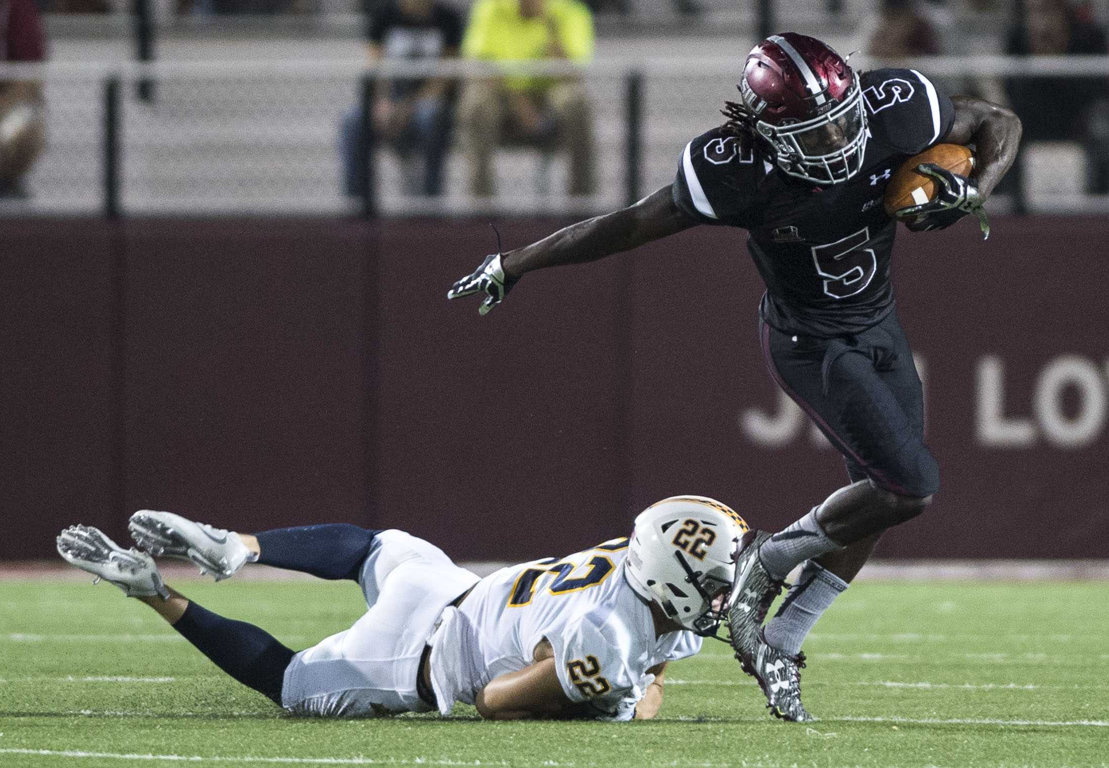 SIU sophomore running back Daquan Isom (5) breaks past Murray State junior defensive back Dylan Boone (22) during the Salukis' 50-17 win over the Racers on Saturday, Sept. 17, 2016, at Saluki Stadium. (Ryan Michalesko | @photosbylesko)