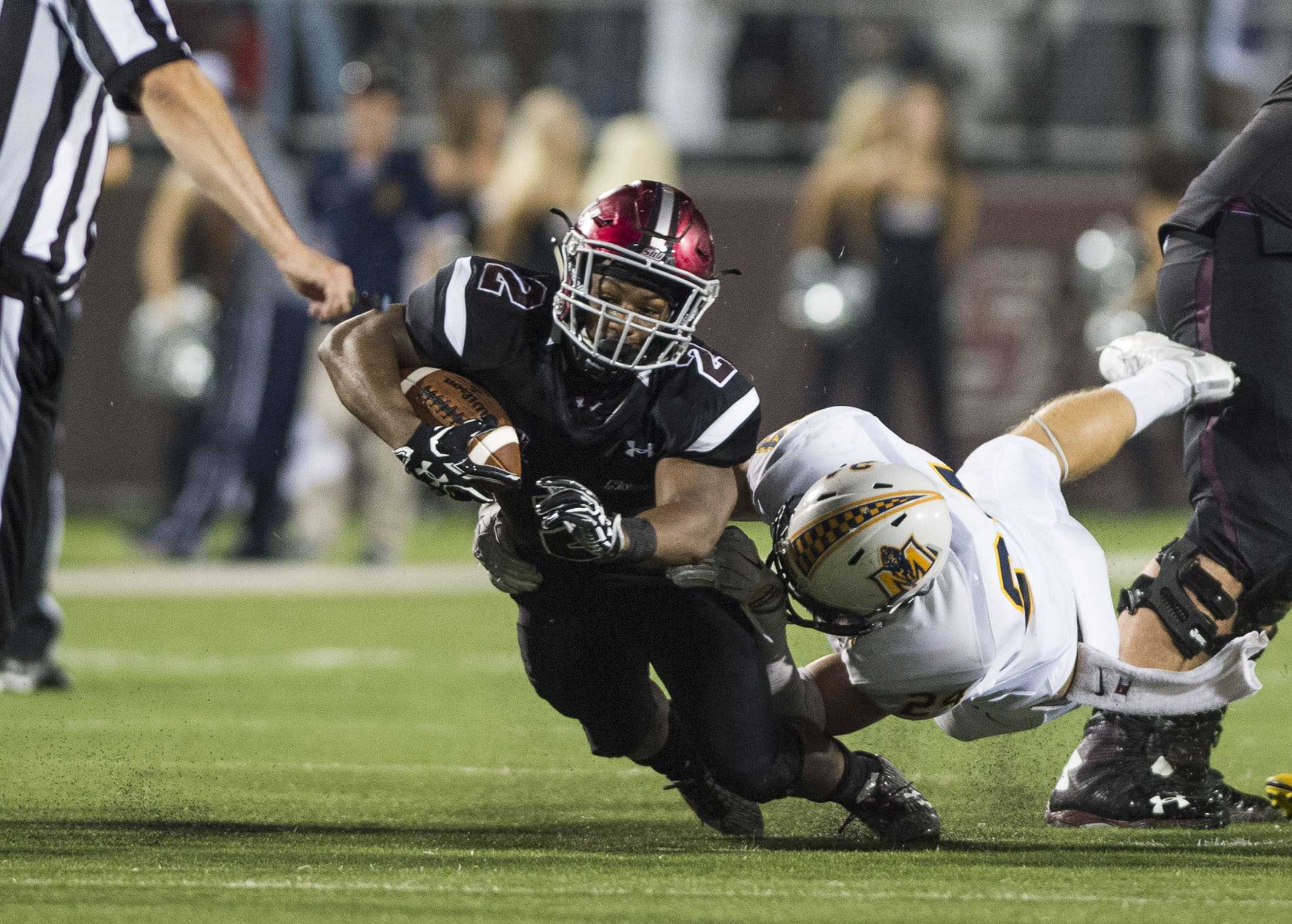 SIU senior running back Aaron Stanton (2) is brought down by Murray State senior defensive back Toby Omli (24) during the Salukis' 50-17 win over the Racers on Saturday, Sept. 17, 2016, at Saluki Stadium. (Ryan Michalesko | @photosbylesko)
