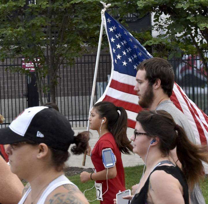 Carbondale+High+School+student+Jenna+Gomez%2C+15%2C+runs+with+the+American+flag+at+the+start+of+the+Saluki+Kickoff+5K+and+Run+to+Remember+9%2F11+on+Saturday%2C+Sept.+10%2C+2016%2C+at+Saluki+Stadium.+%28Athena+Chrysanthou+%7C+%40Chrysant1Athena%29