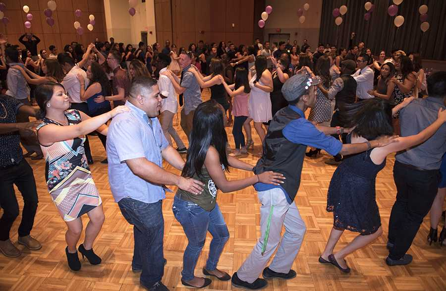Attendees of SIU's Noche de Gala event form a conga line on the dance floor Saturday, Sept. 24, 2016, at the Student Centre ballrooms. (Morgan_Timms | @Morgan_Timms)
