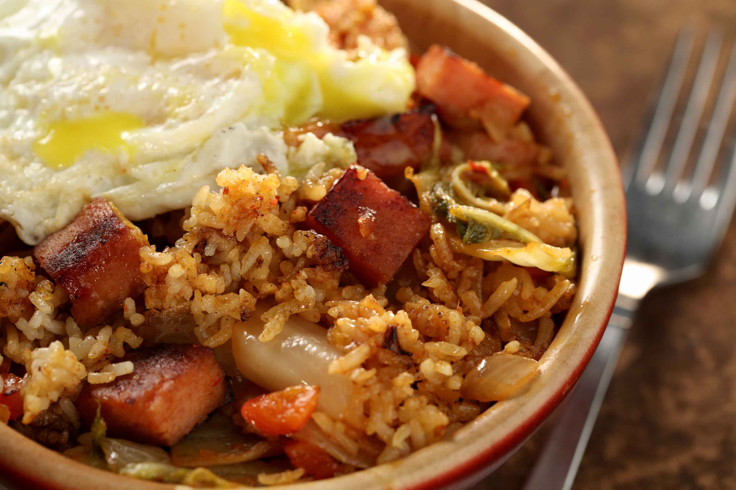 Spam is first cooked with maple syrup for a carmelized glaze that balances the saltiness, tehn tossed with kimchee and a spicy sauce for an up-all-night-and-we're-hungry fried rice. (Michael Tercha/Chicago Tribune/TNS)
