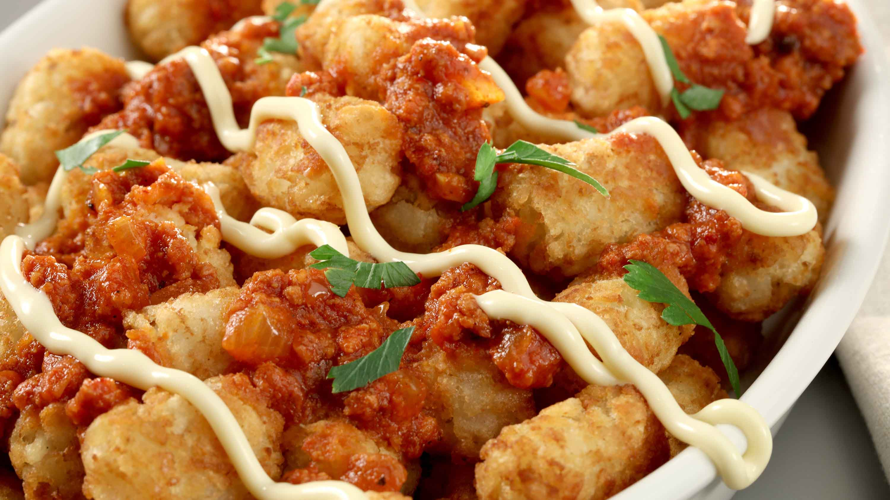 Tater Tots are transformed into pa-tot-as bravas, a play on the Spanish dish patatas bravas, with a spicy tomato-chorizo sauce, plus mayo and parsley. (Michael Tercha/Chicago Tribune/TNS)