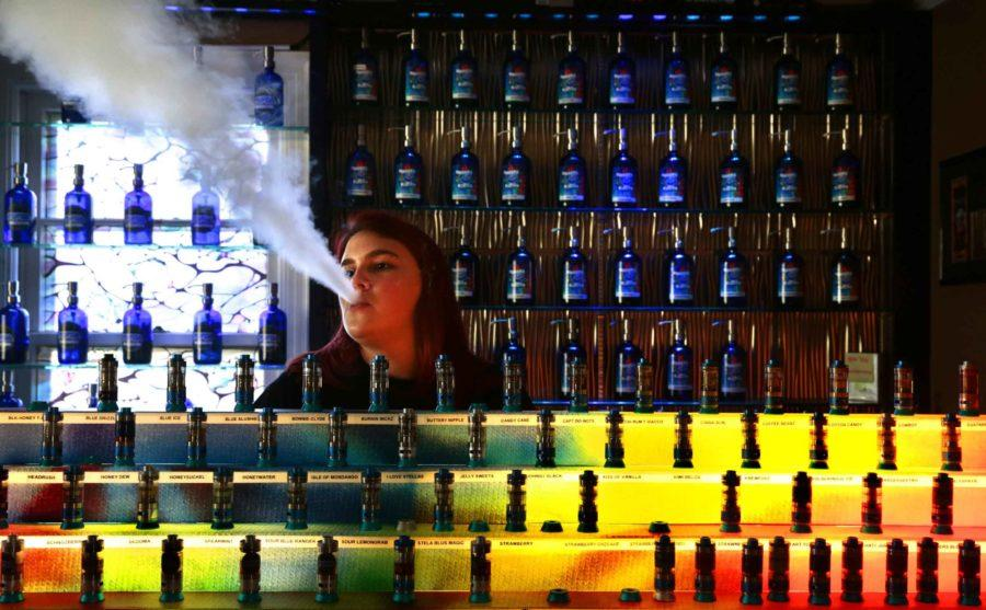 Surrounded by about 100 custom flavor juices and sample tanks, Mallory Immethun, 20, vapes while awaiting customers at Stella Blues Vapors on Wednesday, Sept. 7, 2016 in Fenton, Mo. (Robert Cohen/St. Louis Post-Dispatch/TNS)