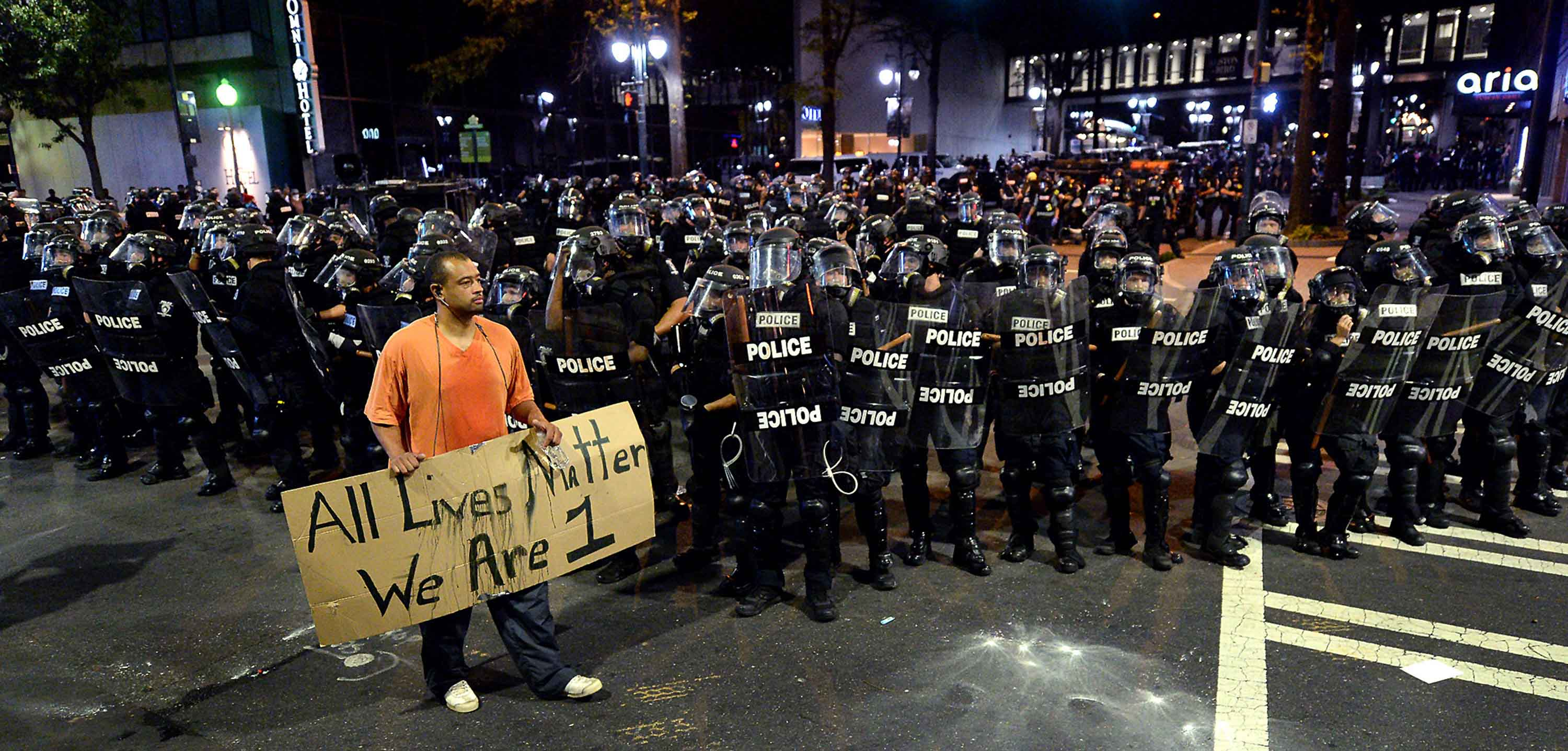 A protestor walks in front of Charlotte officers in riot gear with a sign reading