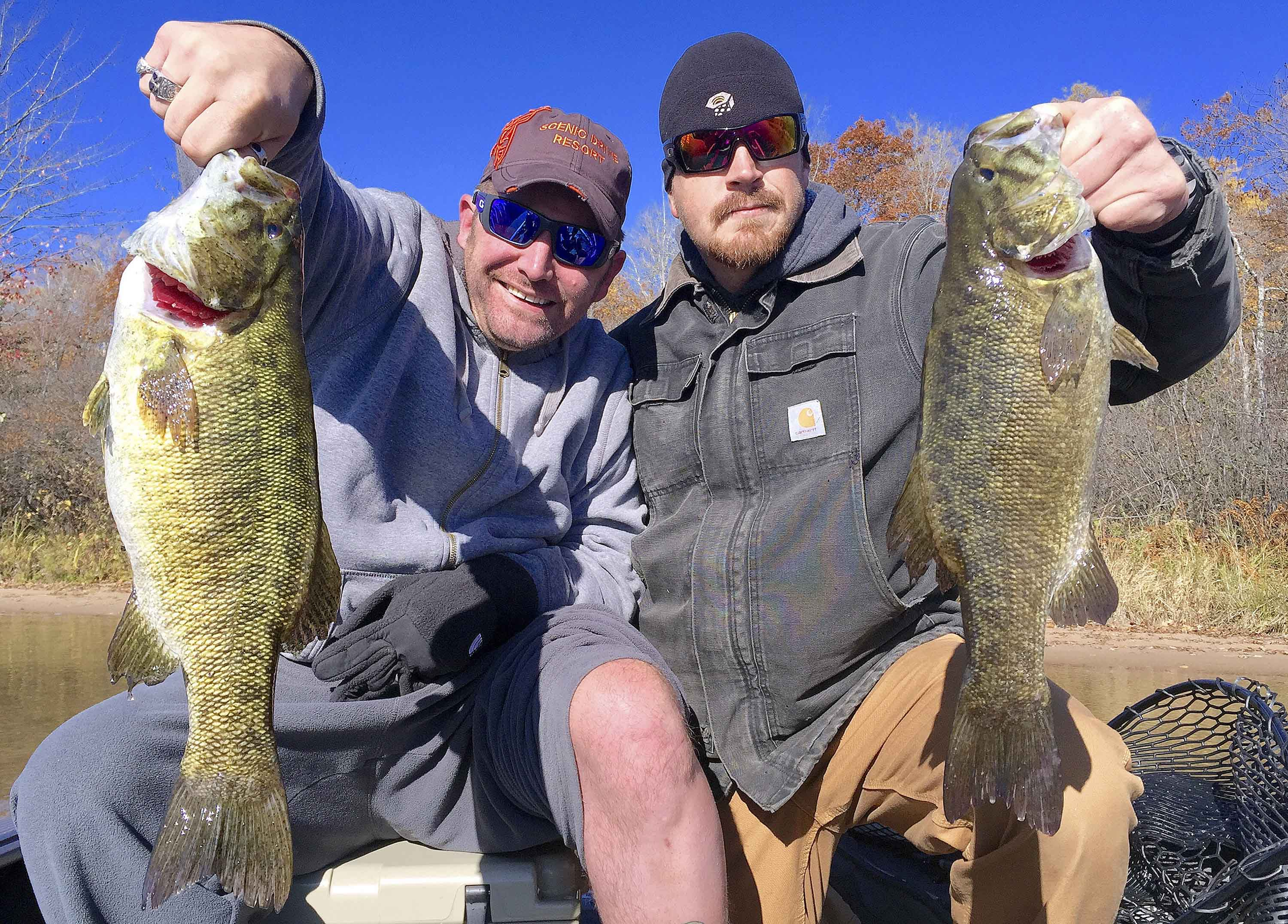 Wounded veterans Tony Simone, left, of Joliet, Ill., and Josh Krueger of Hubertus, Wis., show off a pair of 20-inch smallmouth bass they caught while fishing on Oct. 16, 2015. (Sam Cook/Duluth News Tribune/TNS)