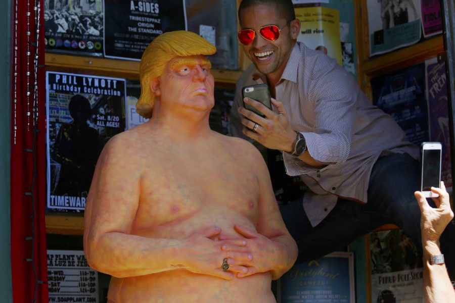 Jason Burch, 38, right, of West Hollywood, takes a selfie with a nude statue depicting Donald Trump at the entrance of Soap Plant Wacko in the Los Feliz neighborhood of Los Angeles on Thursday, Aug. 18, 2016. A Florida man was recently arrested for allegedly stealing a similar statue. (Francine Orr/Los Angeles Times/TNS)