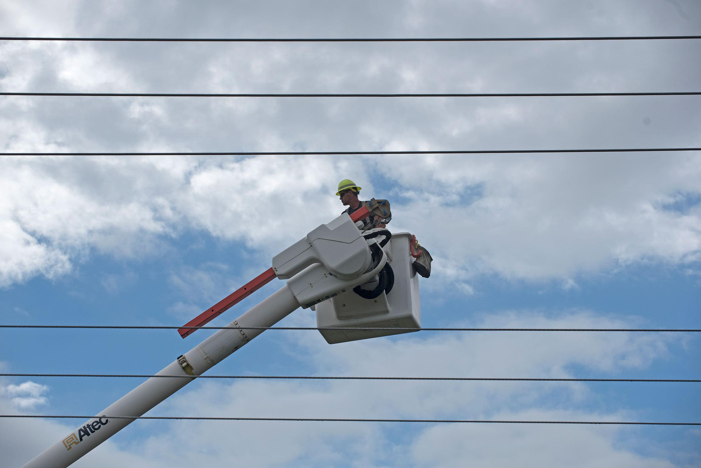 "Neil Sizemore, of Carterville, inspects power lines Friday, Sept. 30, 2016, on Wall Street in Carbondale. Sizemore has worked for the Ameren power company for more than two decades. ""I just needed a job,"" said Sizemore, who also operates a farm in Carterville. ""[It's] a way to make a living."" The lineman said his father, two uncles and three brothers have worked in the profession. (Jacob Wiegand 