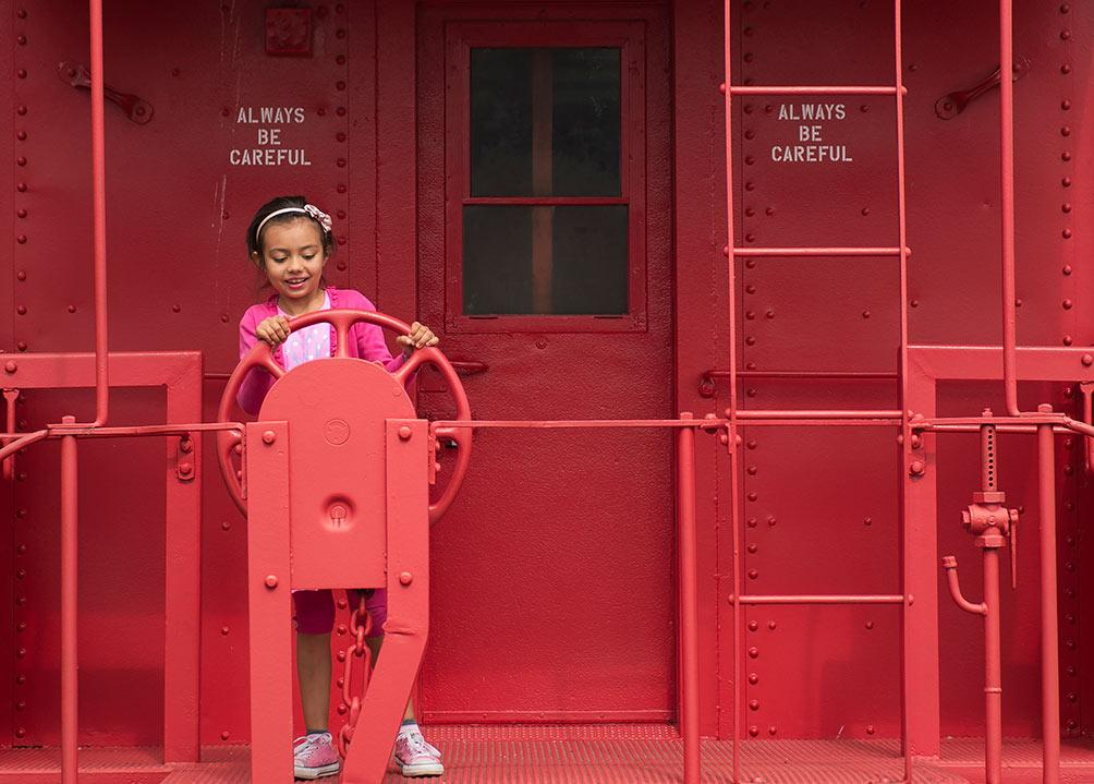"""Myla Reyes, 7, of Carbondale, plays on a retired train caboose Sunday, Oct. 2, 2016, in downtown Carbondale. """"I like to climb on things,"""" Reyes said. """"It's really fun."""" She said sitting on the roofs on the train cars was her favorite part of the experience. (Jacob Wiegand 