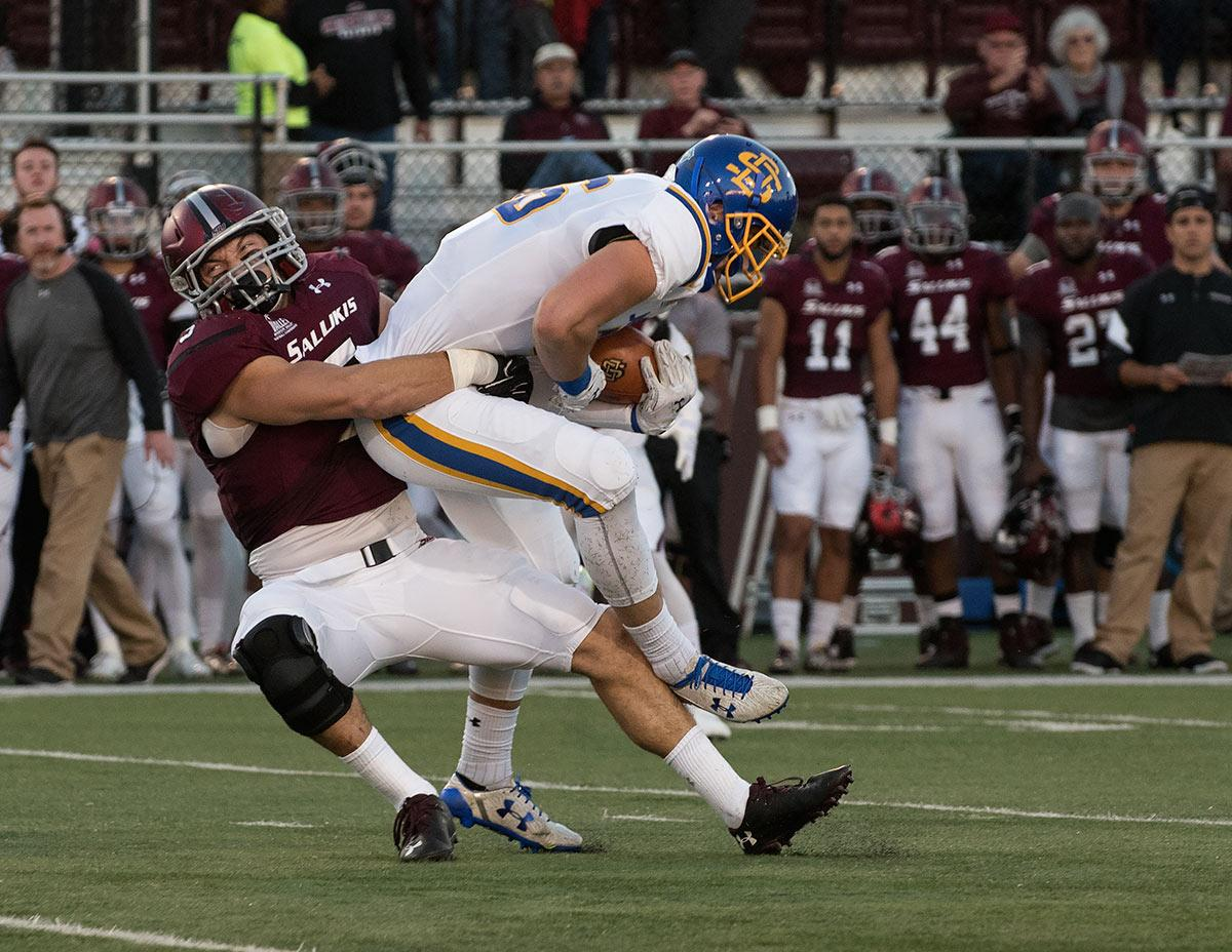 Saluki senior inside linebacker Chase Allen tackles Jackrabbit junior tight end Dallas Goedert during the first half of the SIU's 45-39 loss to South Dakota State on Saturday, Oct. 8, 2016, at Saluki Stadium. (Jacob Wiegand | @JacobWiegand_DE)