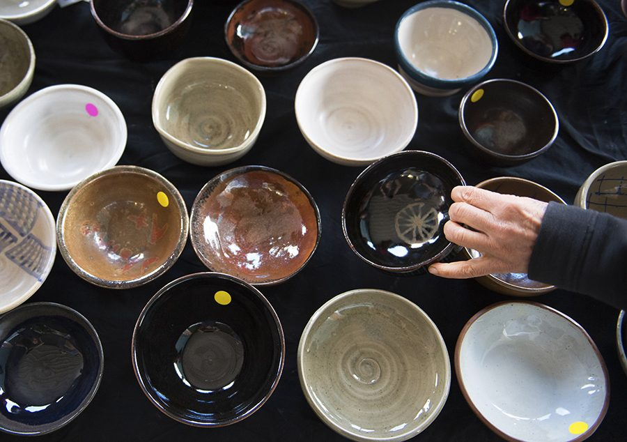 An+attendee+of+the+SIU+School+of+Art+and+Design+and+Southern+Clay+Works%27+Empty+Bowls+fundraiser+selects+one+of+many+ceramic+bowls+for+sale+Saturday%2C+Oct.+15%2C+2016%2C+outside+The+Neighborhood+Co-op+Grocery+in+Carbondale.+%28Morgan+Timms+%7C+%40Morgan_Timms%29