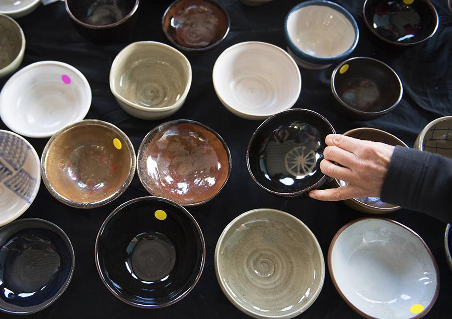 An attendee of the SIU School of Art and Design and Southern Clay Works' Empty Bowls fundraiser selects one of many ceramic bowls for sale Saturday, Oct. 15, 2016, outside The Neighborhood Co-op Grocery in Carbondale. (Morgan Timms | @Morgan_Timms)