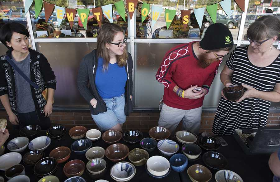 "Nik Price, a graduate student in printmaking from Mankato, Minn., inspects the design on a ceramic bowl held by SIU associate professor of ceramics Pattie Chalmers, alongside graduate students in ceramics Yen-Ting Chiu, of Taipei, Taiwon, and Kari Woolsey, of Boca Raton, Fla., on Saturday, Oct. 15, 2016, during the Empty Bowls fundraiser outside The Neighborhood Co-op Grocery in Carbondale. Chalmers said the best part of the event will be giving a big check to the Good Samaritan House. ""It's also been great meeting the community and for the students, the makers of the bowls, to be out here selling their creations,"" Chalmers said. (Morgan Timms 