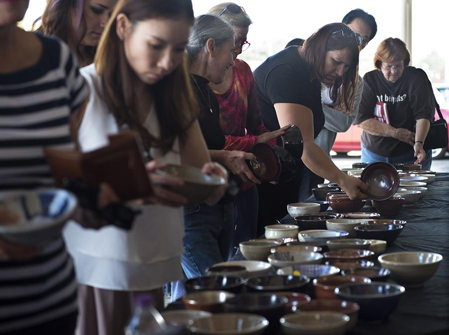 Attendees of the SIU School of Art and Design and Southern Clay Works' Empty Bowls fundraiser queue alongside a table filled with ceramic bowls Saturday, Oct. 15., 2016, outside The Neighborhood Co-op Grocery in Carbondale. (Morgan Timms | @Morgan_Timms)