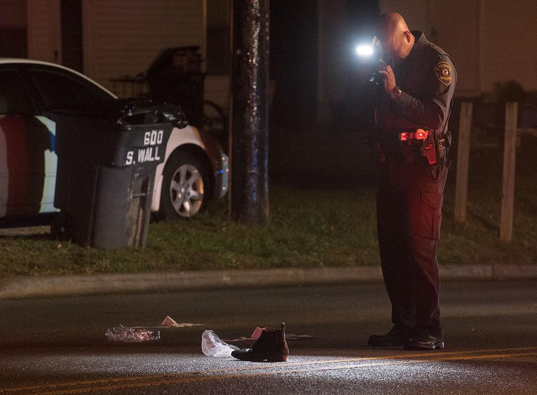 Officer Zach Street, a crash reconstructionist for the Carbondale Police Department, takes a picture of a shoe after a pedestrian was hit by a car Saturday, Oct. 15, 2016, in the 600 block of South Wall Street in Carbondale. (Jacob Wiegand | @JacobWiegand_DE)