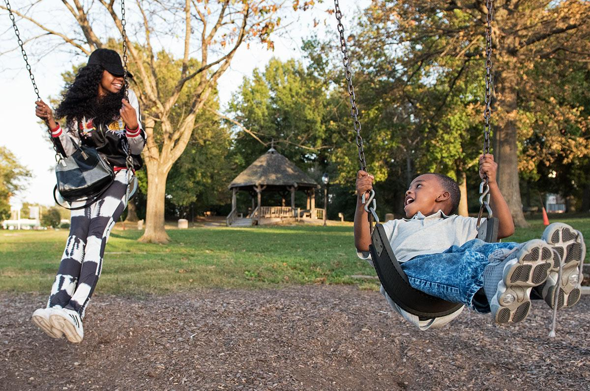 Alicia Hammond, a junior from Kankakee studying healthcare management, swings beside her son, Ryan Simington Jr., 4, on Monday, Oct. 17, 2016, at Lenus Turley Park in Carbondale. Hammond, a single mother and a full-time SIU student, recently started her own clothing line called