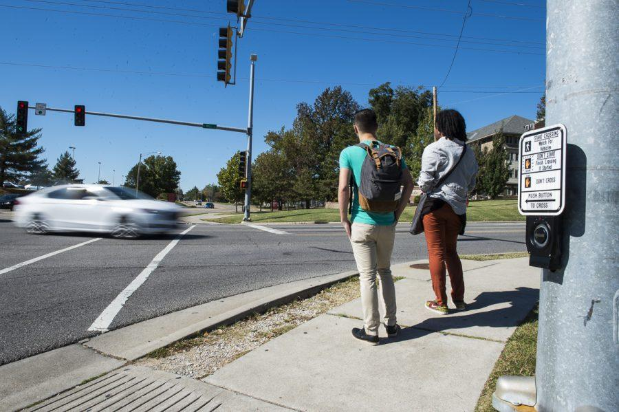 Michael Serna, left, a senior from Modesto, Calif., studying economics, and Kevin Parker, a freshman from Chicago studying architecture, wait to cross the street Sunday, Oct. 23, 2016, at the intersection of South Wall Street and East Grand Avenue in Carbondale. (Ryan Michalesko | @photosbylesko)