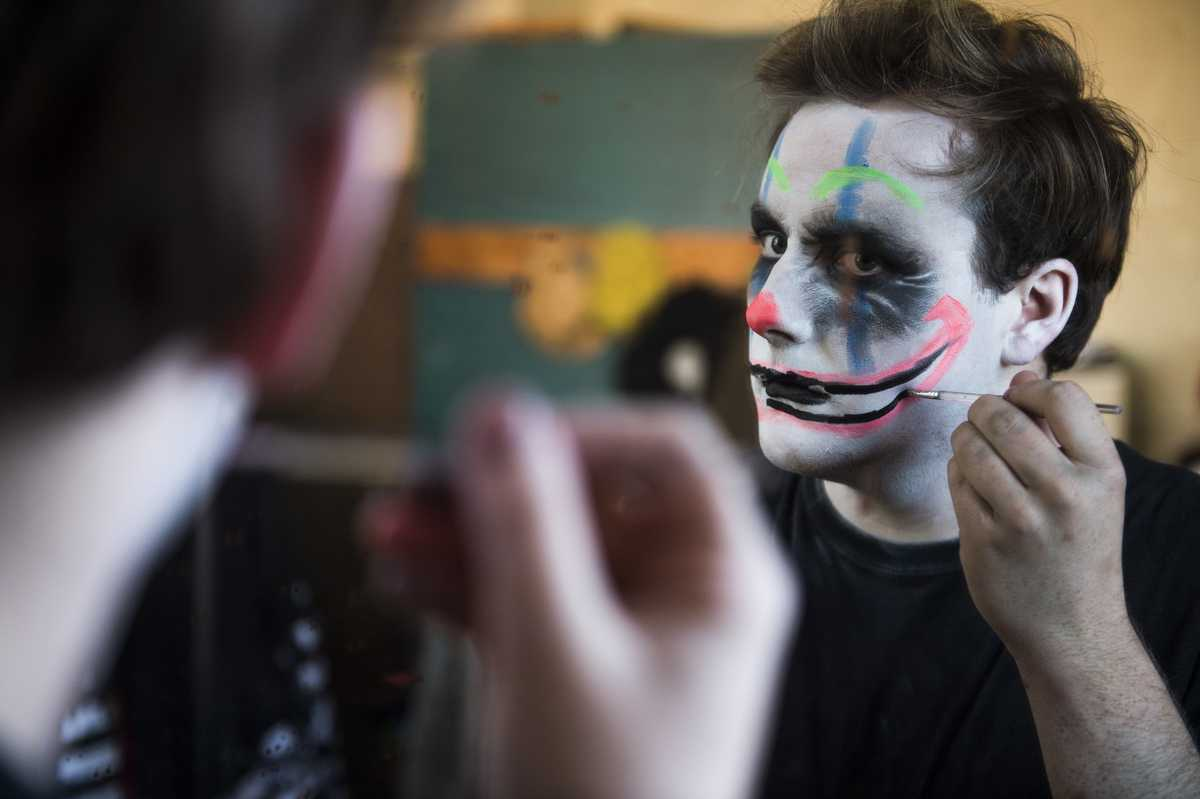 Patrick Burke, a junior from Los Angeles studying theater, applies costume makeup Sunday, Oct. 23, 2016, at Chittyville School Haunted House in Herrin. (Ryan Michalesko | @photosbylesko)