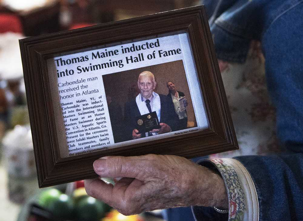 Shirley Maine holds a framed Carbondale Times article about her husband's induction into the International Masters Swimming Hall of Fame on Monday, Oct 17, 2016, in the couple's Carbondale home. (Morgan Timms | @Morgan_Timms)