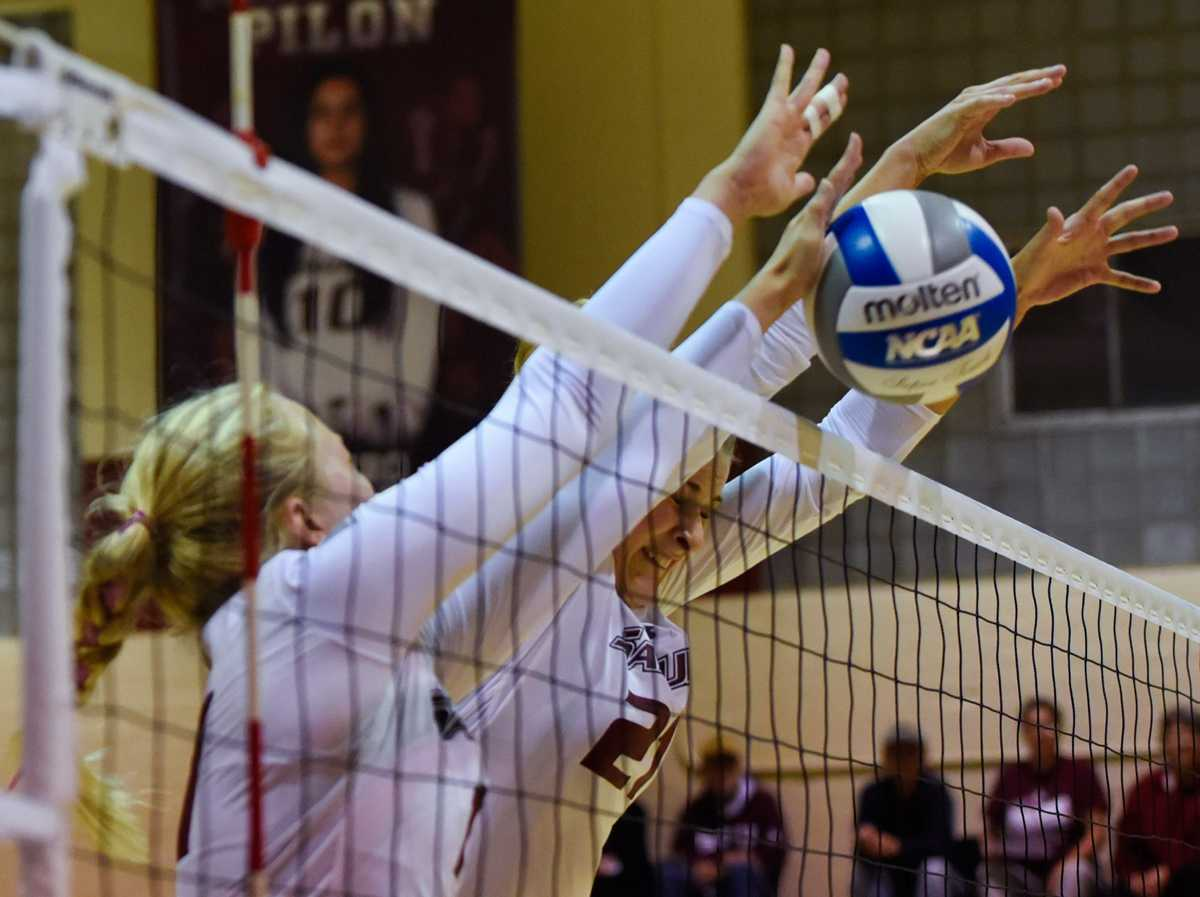 Junior outside hitter Nellie Fredriksson, left, and junior middle hitter Alex Rosignol go for a block during Loyola's 3-1 victory against the Salukis on Friday, Oct. 28, 2016, in Davies Gym. (Sean Carley | @SCarleyDE)