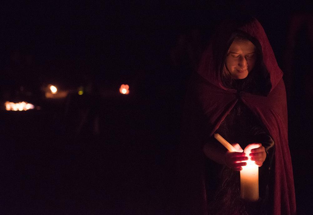 SIU alumna Brenna Carriger, of DeSoto, holds a keepsake at the ancestral altar Saturday, Oct. 29, 2016, during the Southern Illinois Pagan Alliance's Samhain celebration at Crab Orchard Lake. (Morgan Timms | @Morgan_Timms)