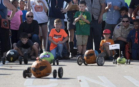 Children watch as their pumpkins race down Mill Street during the the Great Carbondale Pumpkin Race on Saturday, Oct. 29, 2016, near the intersection of Mill Street and South Illinois Avenue. (Morgan Timms | @Morgan_Timms)