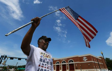 Protester Walter Rice, 75, a life-long Ferguson resident and Vietnam veteran waves, a U.S. flag in front of the Ferguson police department on Tuesday, Aug. 19, 2014, in Ferguson, Mo. (Curtis Compton/Atlanta Journal-Constitution/MCT)