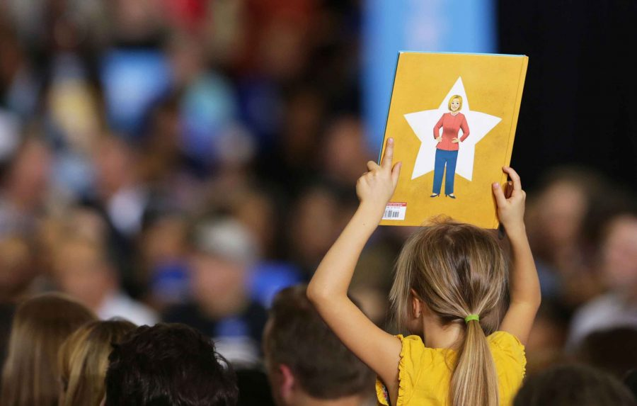 A young supporter of Democratic candidate Hillary Clinton holds up a book that has a drawing of Clinton on the back on the campus of Wayne State University at a voter registration event on Monday, Oct. 10, 2016 in Detroit, Michigan. Regina H. Boone/Detroit Free Press/TNS)