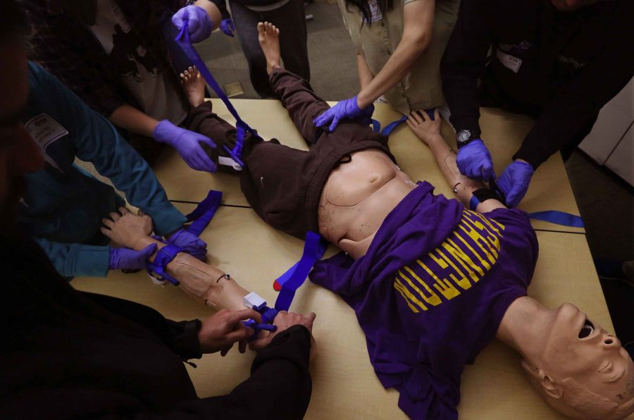 With the help of Hans the manikin, students in the Stop the Bleed program learn how to apply tourniquets at Harborview Medical Center. In emergency situations, severe bleeding is a common cause of death for trauma patients. (Alan Berner/Seattle Times/TNS)