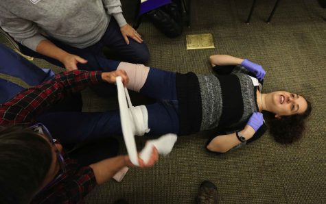 Rachel Abramson role-played a trauma victim as fellow students use gauze to apply pressure to a wound. (Alan Berner/Seattle Times/TNS)