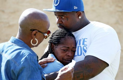 Monique Morgan, the mother of Carnell Snell, is held by a neighbor as they stand beside a makeshift memorial for Morgan's son Sunday morning, Oct. 2, 2016. (Luis Sinco/Los Angeles Times/TNS)