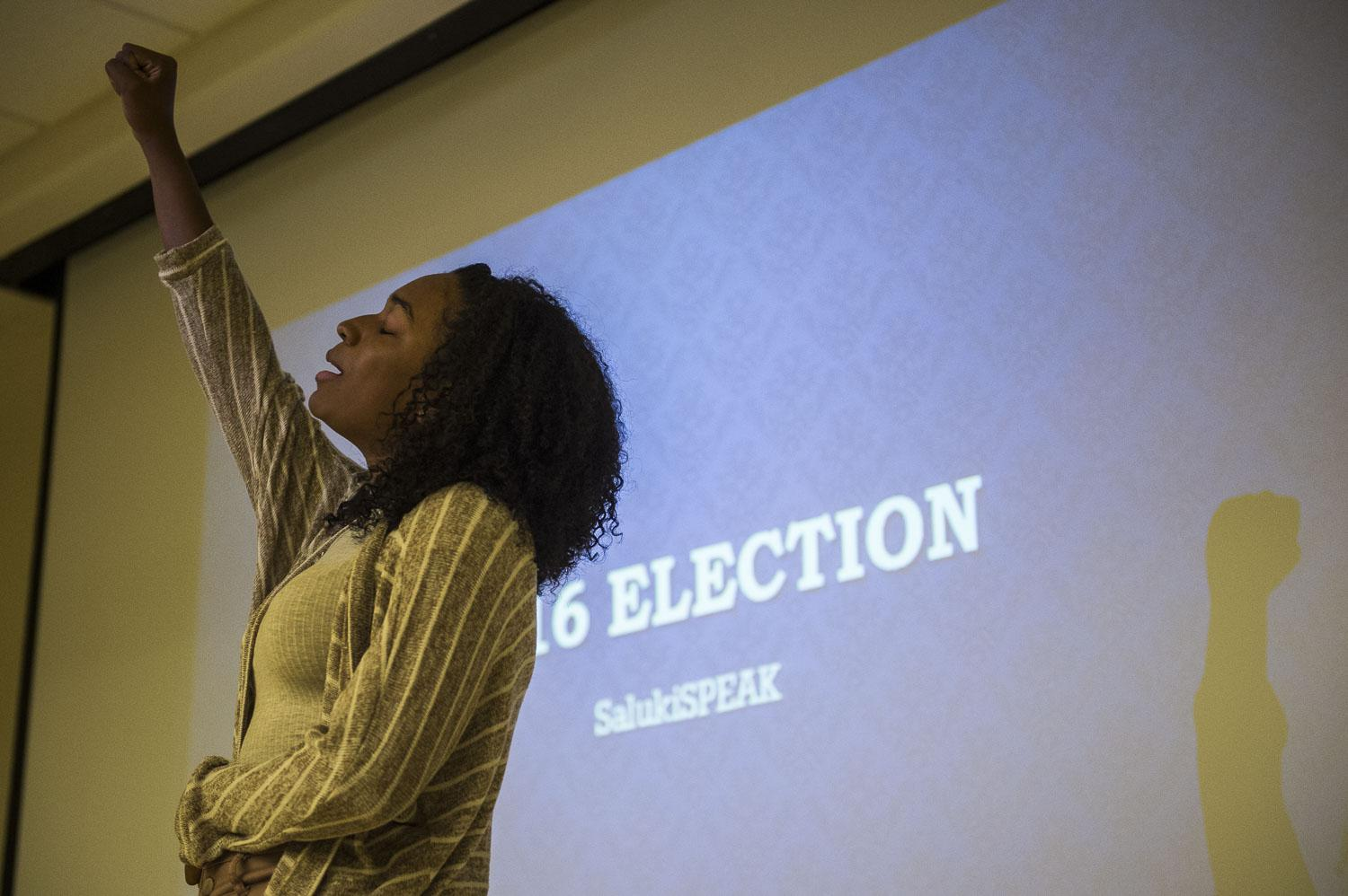 Re'Jean Pink, a freshman from Chicago studying English, raises her fist while reciting a poem Tuesday, Nov. 1, 2016, during a Salukis SPEAK poetry slam at the Student Services Building.