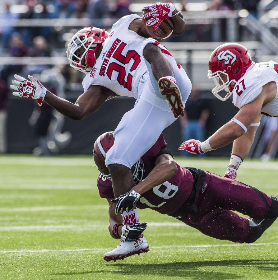 Freshman safety Jeremy Chinn (18) brings down Coyote sophomore running back Paul Anderson (25) on Saturday, Nov. 5, 2016, during the Salukis' 35-28 win against the University of South Dakota Coyotes at Saluki Stadium. (Daily Egyptian File Photo)