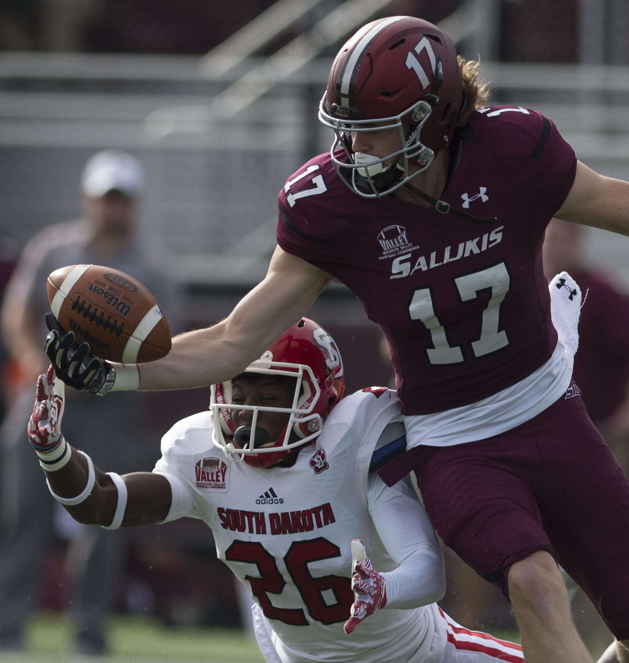 Senior wide receiver Billy Reed (17) reaches to recieve a pass as South Dakota sophomore defensive back Danny Rambo (26) attempts to intercept Saturday, Nov. 5, 2016, during the Salukis' 35-28 win against the University of South Dakota Coyotes at Saluki Stadium. (Ryan Michalesko | @photosbylesko)