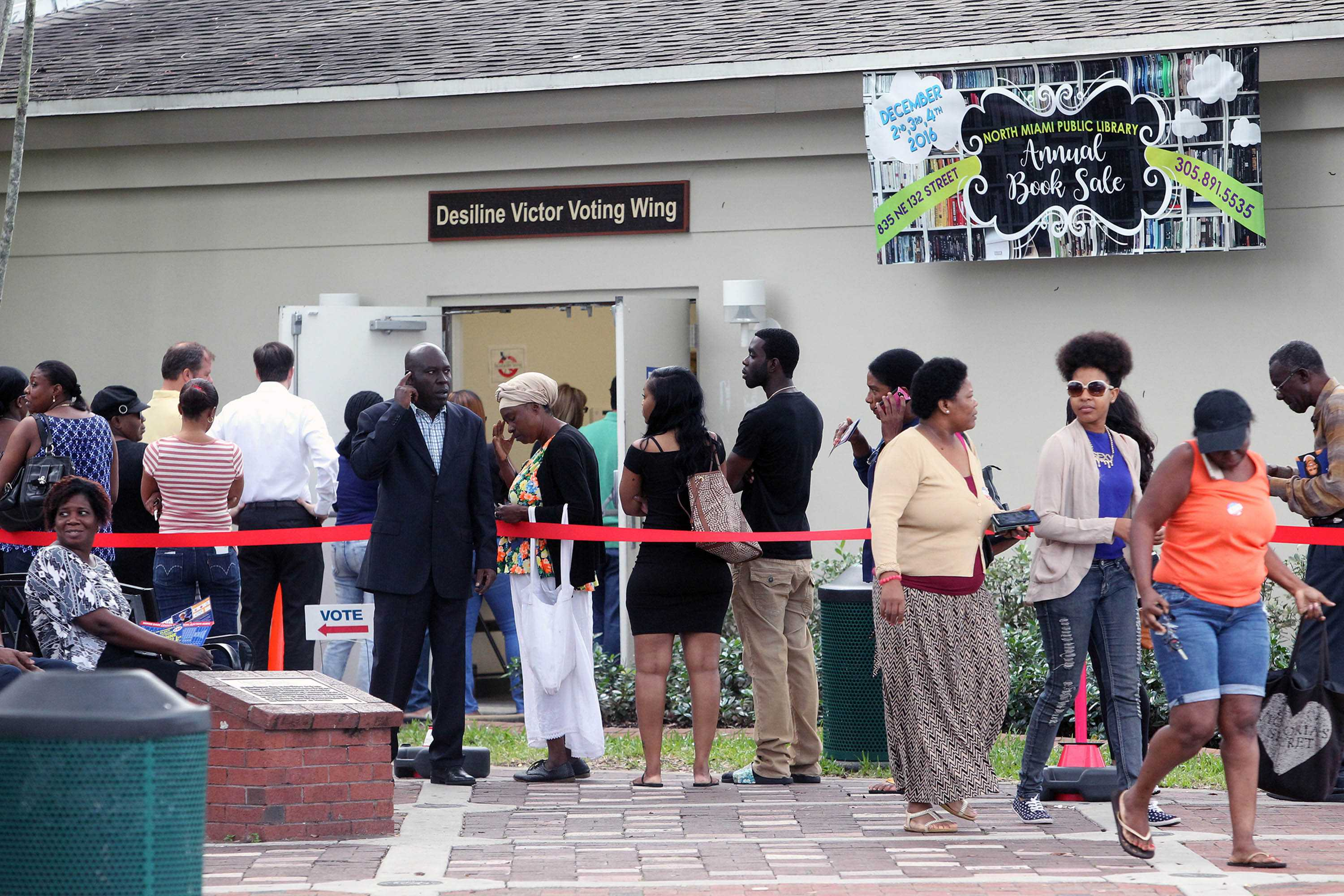 A group of people stand in line waiting to vote early outside the North Miami Public Library on Friday, Nov. 4, 2016. (Roberto Koltun/Miami Herald/TNS)
