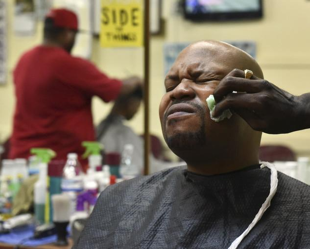 Taliq Montegomery grimaces as barber Terrence Upchurch rubs after shave on his face on Wednesday, Nov. 2, 2016, at Arnette's barber shop. (Anna Spoerre | @annaspoerre)
