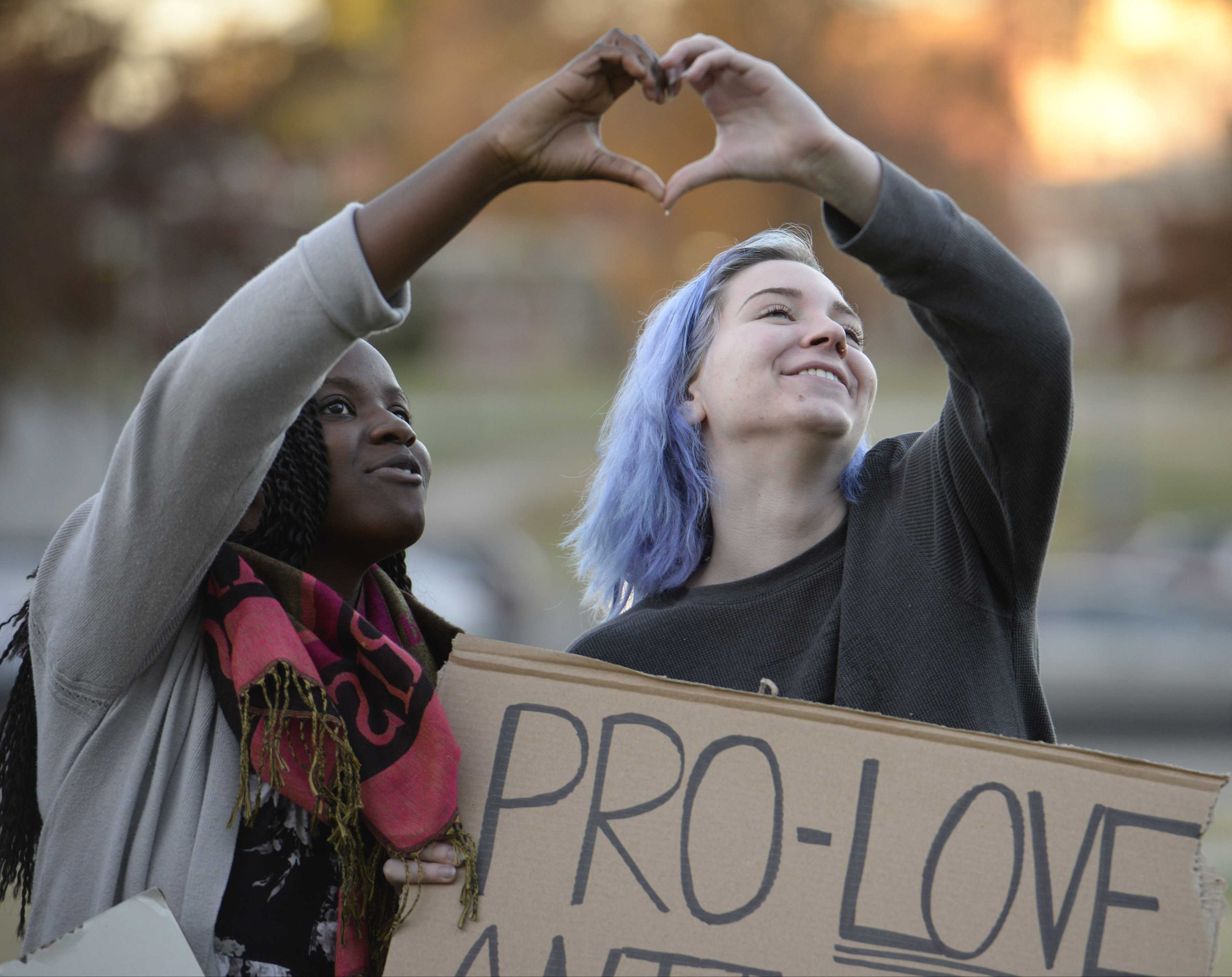 Oreoluwa Ojewuyi, left, and Brynn Kosmicki form a heart with their hands as they dance and sing to