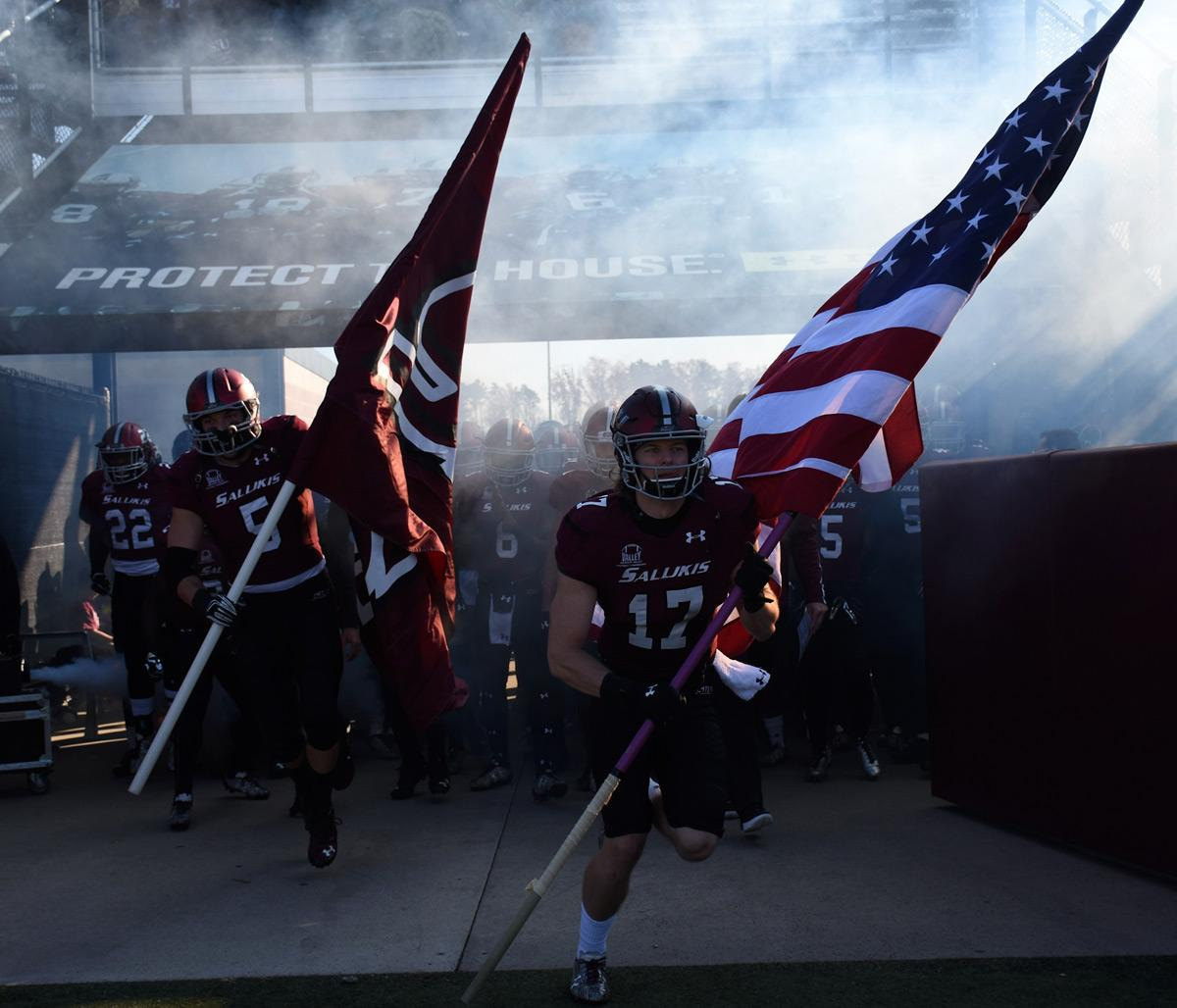 Senior wide receiver Billy Reed (17) and senior linebacker Chase Allen (5) run onto the field with flags before the Salukis' 44-34 win against Western Illinois on Saturday, Nov. 19, 2016, at Saluki Stadium. (Athena Chrysanthou | @Chrysant1Athena)