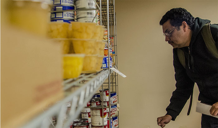 """Guillermo Reyes, a doctoral candidate in education from Nicaragua, browses for food Monday, Nov. 21, 2016, at the Saluki Food Pantry in the Student Center. """"I have three children,"""" Reyes said. """"So this is helpful as an international student."""" Reyes said it's hard to make ends meet with an assistantship position. """"I have to think very wisely how to spend my money,"""" Reyes said. He said it's important to have money saved for an emergency. """"My son is 8 years old, and he had two MRIs, the first of which he didn't have any medical insurance,"""" he said. """"I am still paying the bills. It's hard."""" (Autumn Suyko 