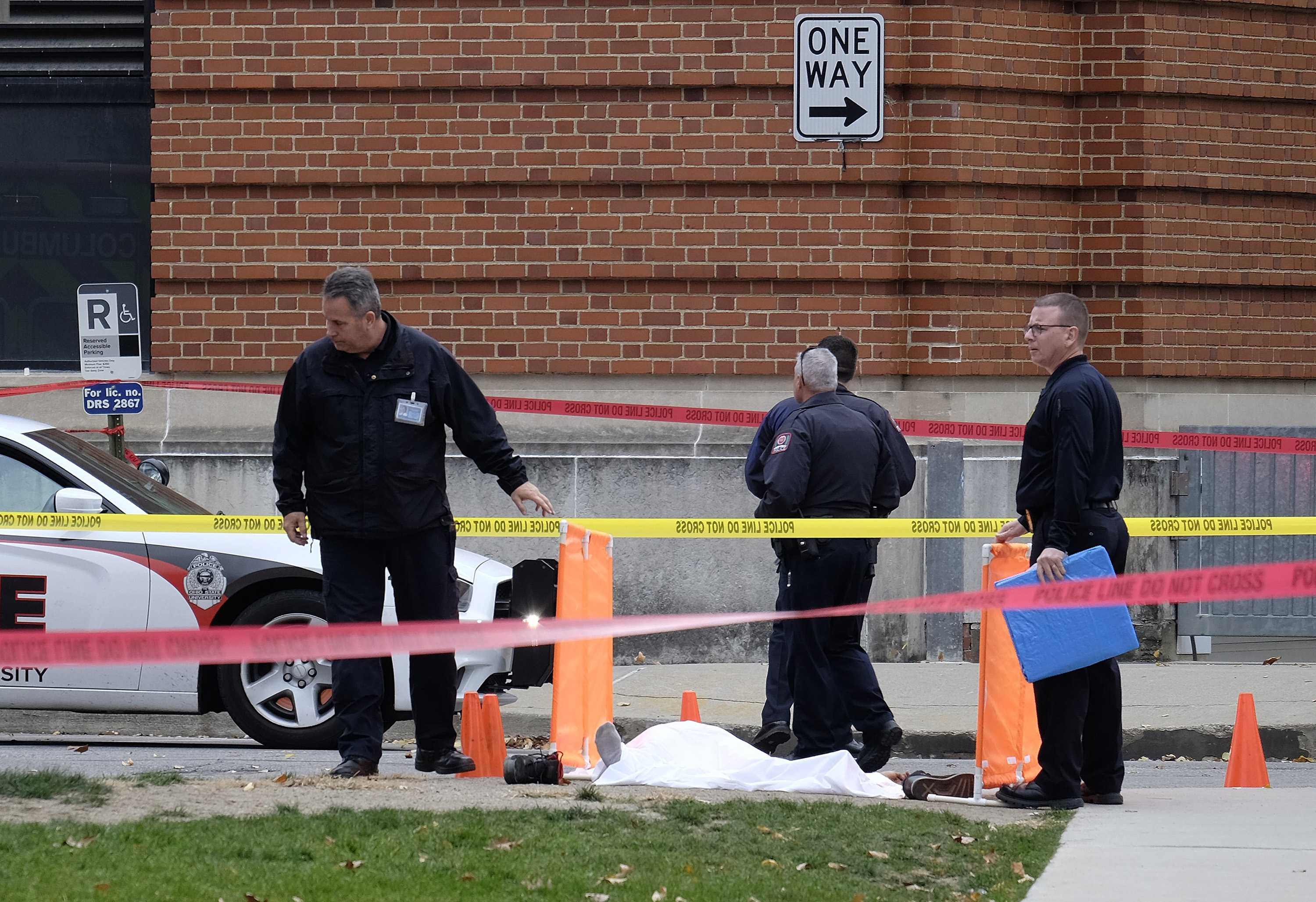 Police cover the body of a suspect along 19th Avenue outside Watts Hall on Ohio State's campus following a vehicular assault and stabbing on Nov. 28, 2016 in Columbus, Ohio. (Adam Cairns/The Columbus Dispatch/TNS)