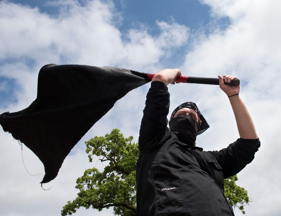 A protester, who refused to give his name, waves a black flag May 2 during the May 2 Strike Committee's protest outside Faner Hall in Carbondale. More than 100 people marched around campus yelling,