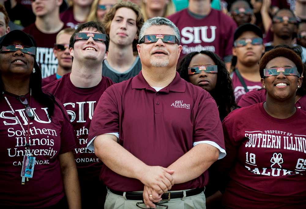 Surrounded by incoming freshman and new students, interim Chancellor Brad Colwell, center, wears a pair of solar eclipse glasses for a group photo following the convocation ceremony Friday, August 19, 2016, at SIU Arena. (Ryan Michalesko | DailyEgyptian.com)