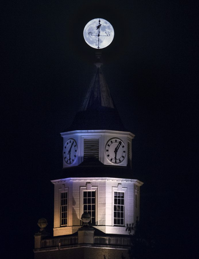 "The Pulliam Hall clocktower weathervane sits silhouetted by the rising superman Monday, Nov. 14, 2016, in Carbondale. A perigee-syzygy, commonly dubbed as a ""supermoon,"" occurs when the moon becomes full on the same day as its perigee, the point in the moon's orbit when it is closest to Earth. The 2016 supermoon appeared larger than at any other point in the last 68 years, and won't appear this large again until 2034, according the NASA. (Ryan Michalesko 