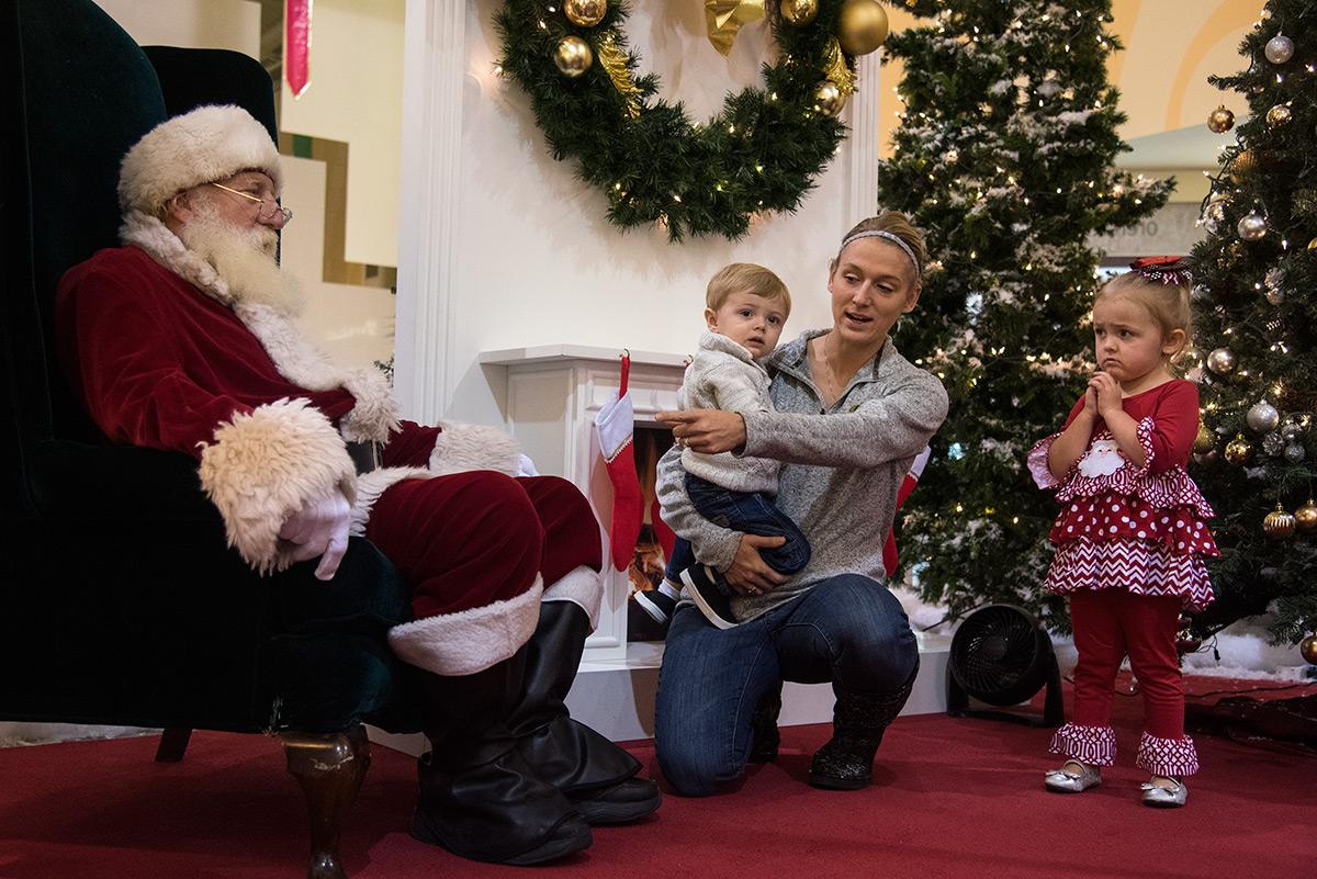 "Callie James, of Carterville, attempts to persuade her children Gunnar James, 1, and Kinley James, 3, to sit with University Mall Santa, Max Luttrell, Wednesday, Nov. 30, 2016, in Carbondale. ""They're always terrified,"" Callie said of her children taking pictures with Santa. ""It's an obligatory picture every year."" This is Luttrell's eighth year portraying Santa at University Mall where he will meet with guests until Christmas Eve. ""[I want to do this] for the enjoyment of the kids and for the overall season to bring joy,"" Luttrell said. ""When you love to do something, it's easy and it's fun."" He said watching the kids' reactions and smiles are some of his favorite aspects of the job."