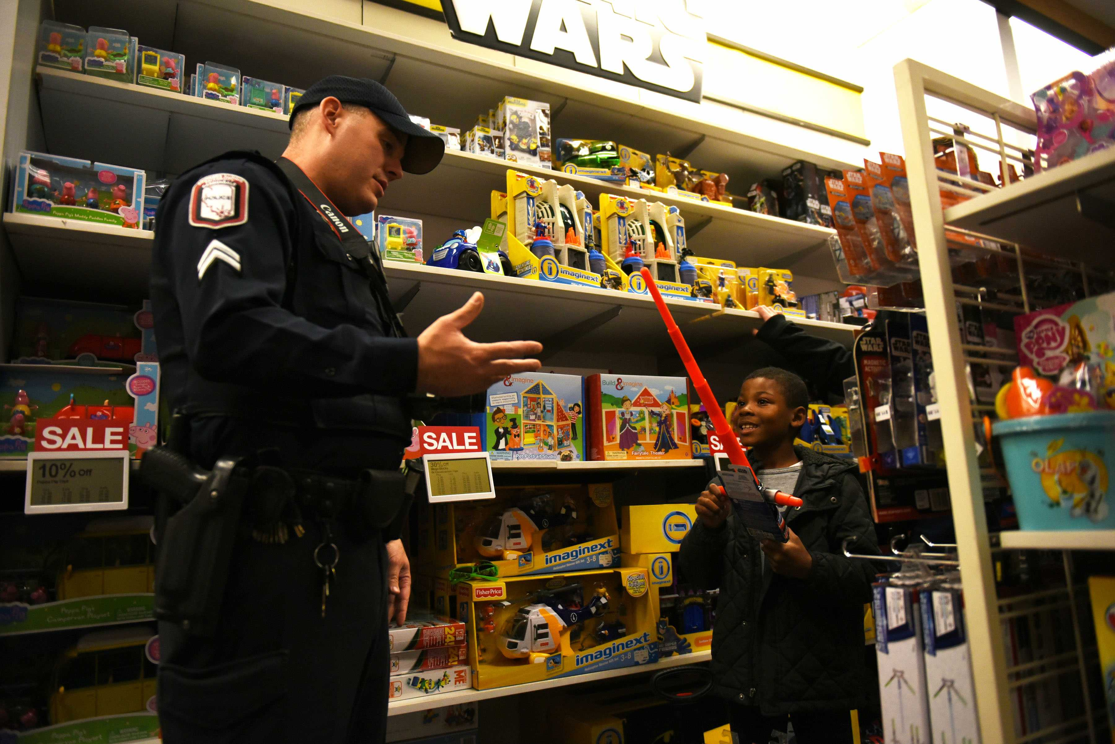 Isaiah McCoy, 8, shows SIU police Cpl. Adam Cunico a toy sword he found during Operation Sergeant Santa, a fifth-annual fundraiser organized by SIU's chapter of Public Relations Student Society of America. Each child paired up with an SIU police officer and PRSSA member to spend the $100 they were given to buy gifts for their families.