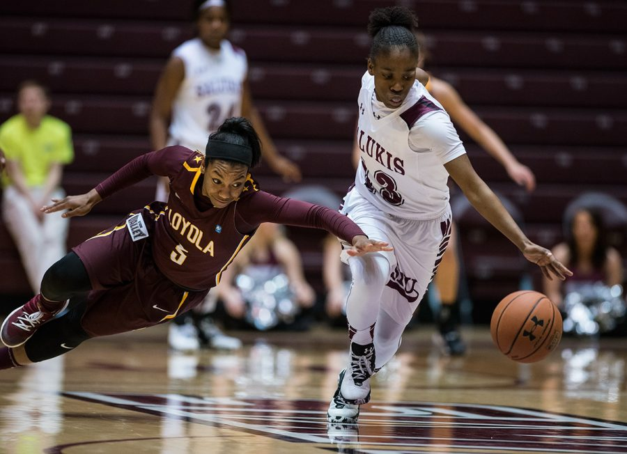 Saluki senior point guard Rishonda Napier and Loyola freshman guard Tiara Wallace lunge for the ball during SIU's 73-57 victory against the Ramblers on Friday, Dec. 30, 2016, at SIU Arena. Napier lead the Salukis in scoring with 20 points. (Jacob Wiegand | jawiegandphoto)