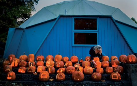 "Lindy Loyd, a Bucky Dome board member, lights jack-o'-lanterns Monday, Oct. 31, 2016, at the Buckminster Fuller Dome Home in Carbondale. The pumpkins, carved by SIU architecture and interior design students, were displayed for visitors and trick or treaters to view. ""No one else is doing anything like this,"" architecture professor Jon Davey said. ""It gives the students a good time."" The students were assigned to carve the pumpkins over the weekend. Amongst nearly 80 pumpkins, designs included the Statue of Liberty, the Eiffel Tower and the U.S. Capitol Building."