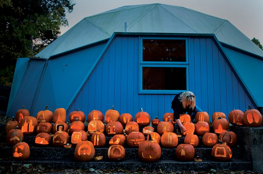 """Lindy Loyd, a Bucky Dome board member, lights jack-o'-lanterns Monday, Oct. 31, 2016, at the Buckminster Fuller Dome Home in Carbondale. The pumpkins, carved by SIU architecture and interior design students, were displayed for visitors and trick or treaters to view. """"No one else is doing anything like this,"""" architecture professor Jon Davey said. """"It gives the students a good time."""" The students were assigned to carve the pumpkins over the weekend. Amongst nearly 80 pumpkins, designs included the Statue of Liberty, the Eiffel Tower and the U.S. Capitol Building."""