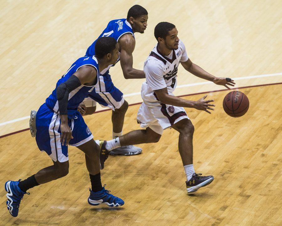 Senior guard Leo Vincent (5) passes the ball as Drake defense trails during the Salukis' 83-69 win against the Bulldogs on Sunday, Jan. 1, 2017, at SIU Arena. (Ryan Michalesko | @photosbylesko)