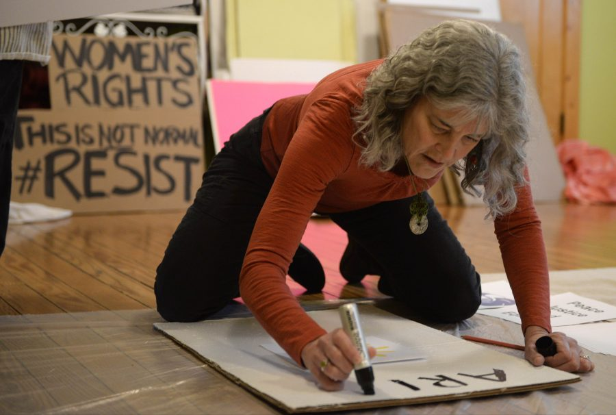 Carbondale resident Jan Eisenhard works on a sign during a gathering of demonstrators Saturday, Jan. 14, 2017, at one | o | one yoga in Carbondale. The signs are meant to be used in a march for women's right on Jan. 21. (Bill Lukitsch | @lukitsbill)