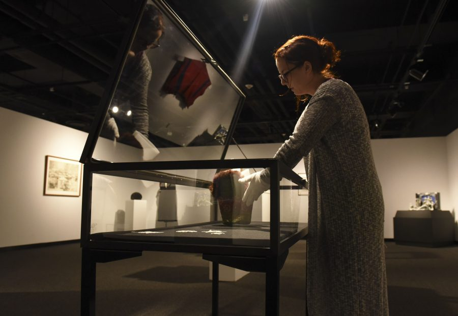 Alison Erazmus, the university's curator of exhibits, places a hat inside a display case Wednesday, Jan. 18, 2017, in the University Museum. (Bill Lukitsch | @lukitsbill)